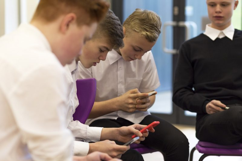 A group of school boys on mobile phones