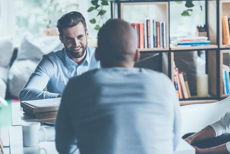 two men talking across desk
