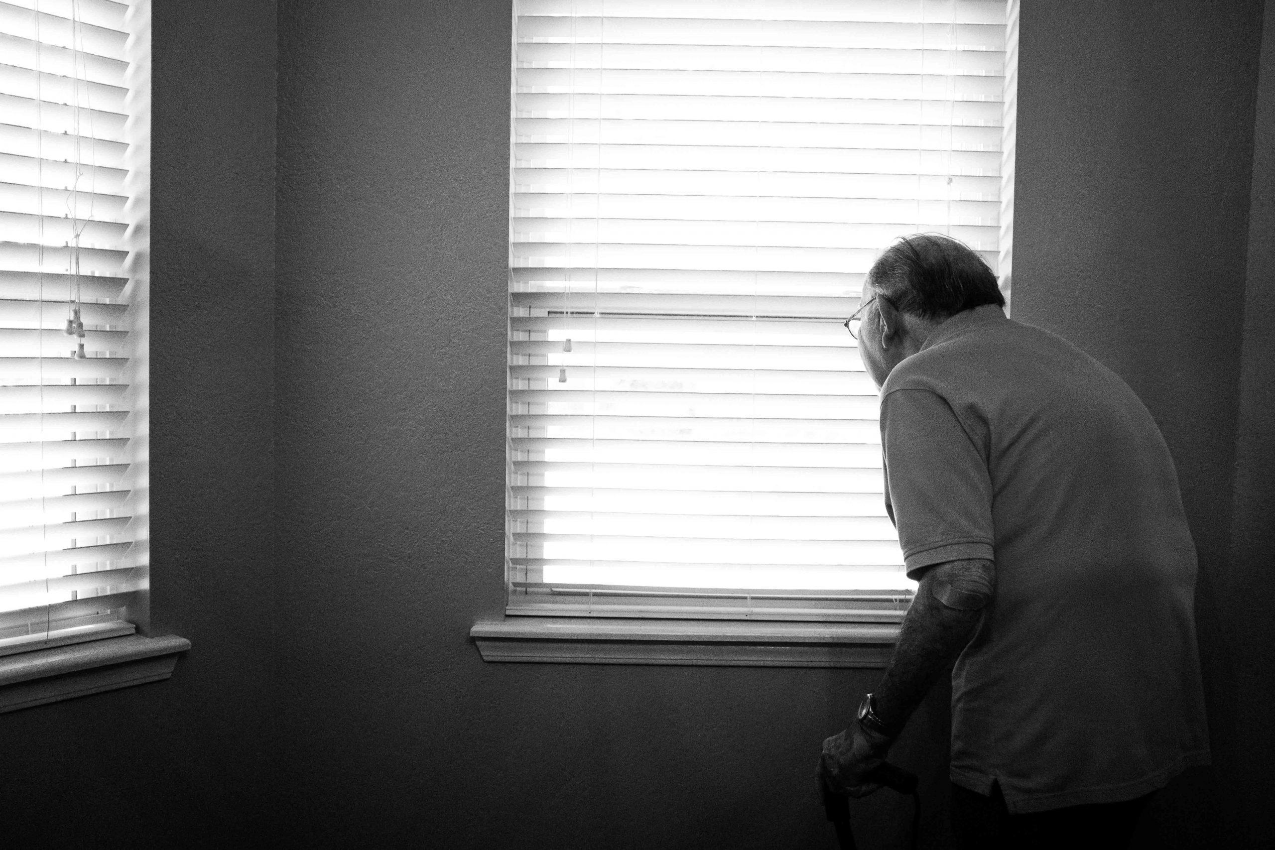 Elderly person looking outside