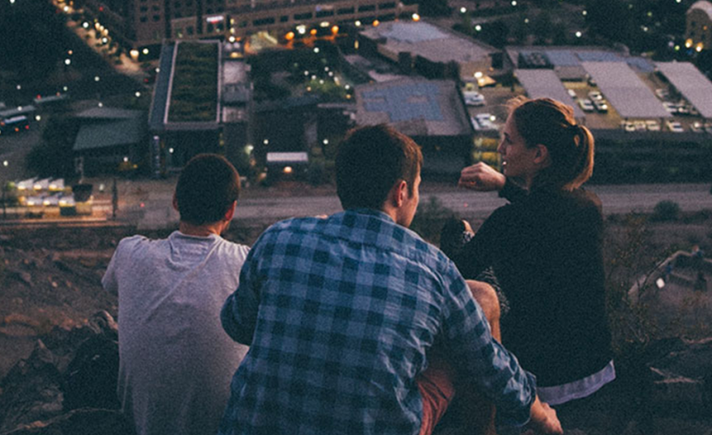 3 young adults sat on a hill at night looking over a town